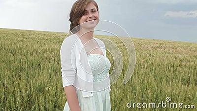 Mo?a bonita entre os spikelets verdes altos do trigo no campo Mulher feliz nova que aprecia o verão, harmonia de humano e filme