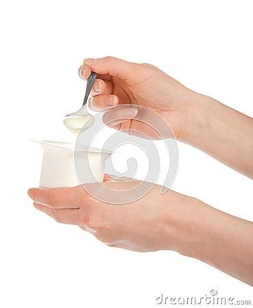 A mão que guarda uma colher com iogurte