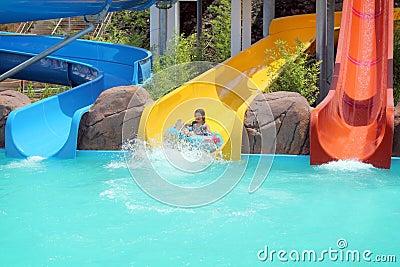 Moça em slideres da piscina