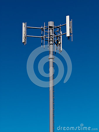 Mobile phone antennas on metal tower on blue sky