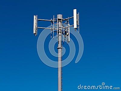 Mobile phone antennas on metal tower on blue sky