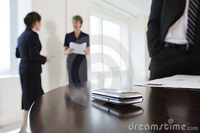 Mobile phone on conference table during meeting.