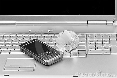 Mobile phone and glass globe on laptop keyboard