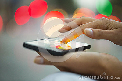 Mobile phone in a woman s hand, city of Light background