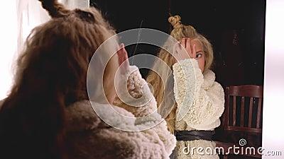 Modèle de mode avec coiffure bouclée en miroir dans le dressing Belle fille en manteau de fourrure blanche posant devant banque de vidéos