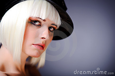 Model with blonde hair and black peaked cap