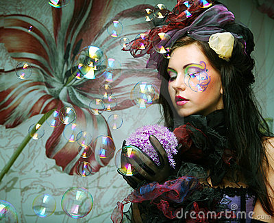 model with creative make-up blowing soap bubbles.