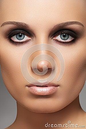 Model with fashion smoky eyes make-up & soft skin