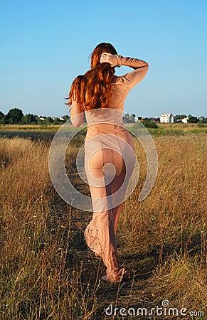Model going on path in long beige dress