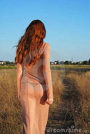 Model going on path in long beige dress, rear view