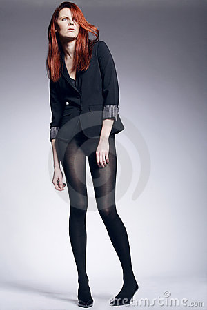 Model with long red hair posing in the studio.