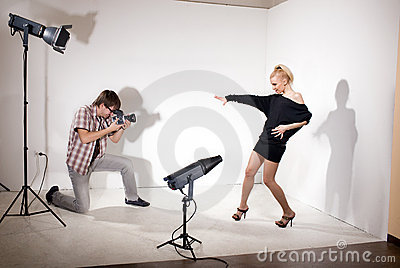 Model poses for photographer in photo studio