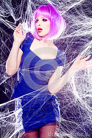 Model with purple wig and intense make-up trapped in a spider web