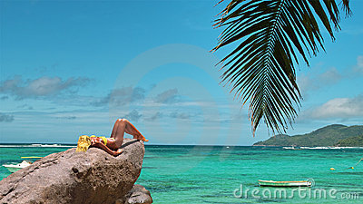 Model is tanning on lagoon beach rock.