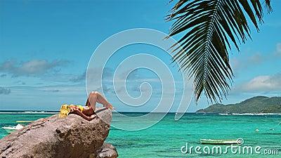 Model is tanning on lagoon beach rock.