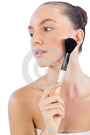 Model touching her face with powder brush