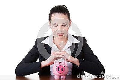 Modello moderno della banca. Donna di affari che si siede con il porcellino salvadanaio.