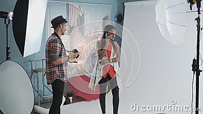 Modelo africano atrativo falando no smartphone enquanto o fotógrafo pede para continuar trabalhando filme