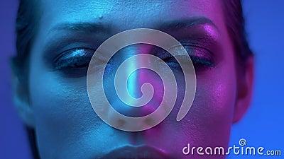 Modelo de forma nas luzes de néon roxas e azuis coloridas que olham com relance fixo e sério na câmera no estúdio vídeos de arquivo