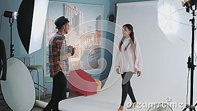 Modelo multiétnico atrativo saltando alto enquanto fotógrafo caucasiano tirando fotos filme