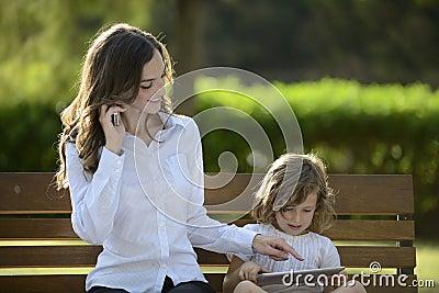 Moder på telefonen med dottern som använder den digitala tableten