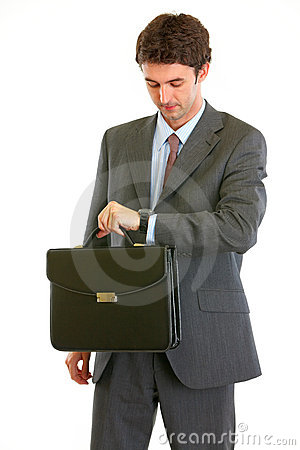 Modern businessman with briefcase checking time