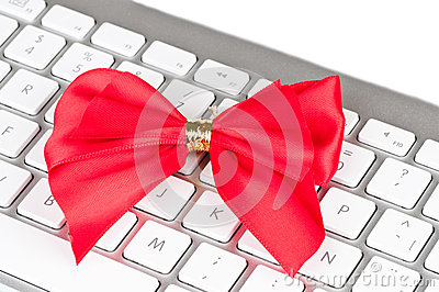 Modern computer keyboard with red bow.