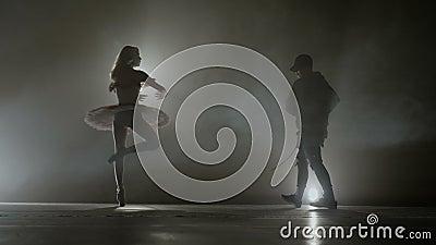 Modern dance battle between a young hip hop dancer versus a graceful beautiful ballerina -. Modern dance battle between a young hip hop dancer versus a graceful stock video footage