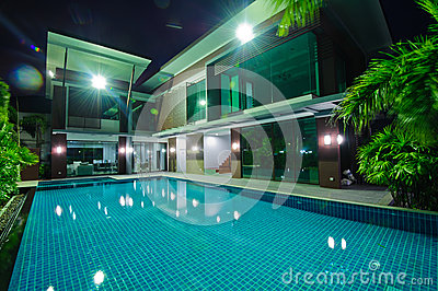 Modern house with swimming pool at night