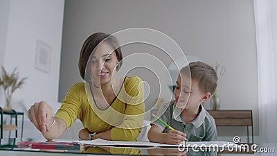 Modern i gult omslag och sonen i t-skjorta sitter på tabellen och drar tillsammans färgblyertspennor på papper lycklig barndom arkivfilmer