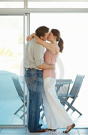 Modern mature couple kissing on the porch