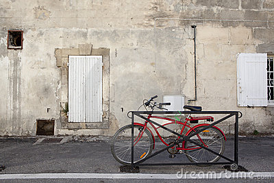 Modern red bicycle in front of an old house