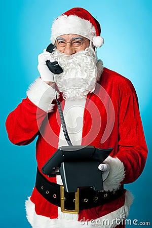 Modern Santa passing greetings over a phone call