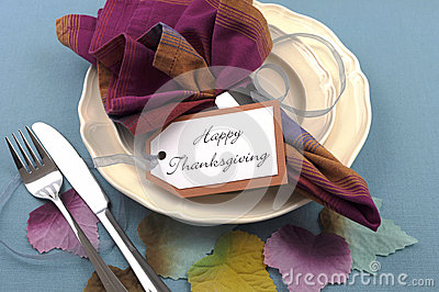 Modern Thanksgiving dining table place setting with autumn leaves