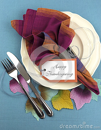 Modern Thanksgiving dining table place setting with autumn leaves - vertical