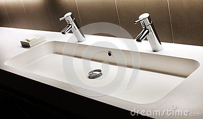 Modern white sink with two shining faucets, tap