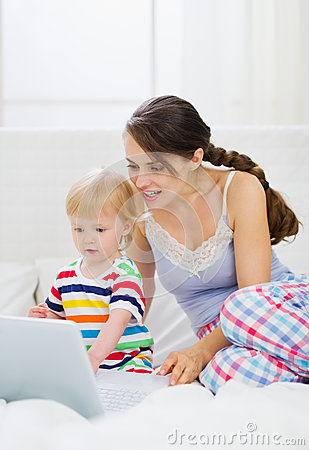 Modern young mother and baby using laptop