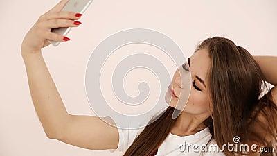 Moderne Jugend schönes langhaariges Europäisch-aussehendes Mädchen mit dem braunen Haar tut selfie auf einem Smartphone nahe eine stock video footage