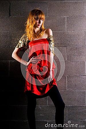 Moderne red-haired Frau in einem roten Kleid des Satins