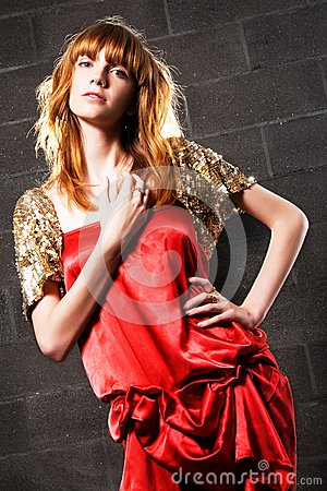 Moderne red-haired Frau in einem roten Kleid des Satins