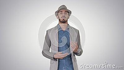 In modieuze positieve vrolijke mens die toevallig overhemd dragen en sunhat en aan camera op gradiënt lopen spreken stock videobeelden