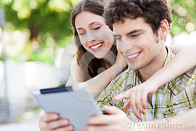 Młodzi ludzie patrzeje cyfrową pastylkę