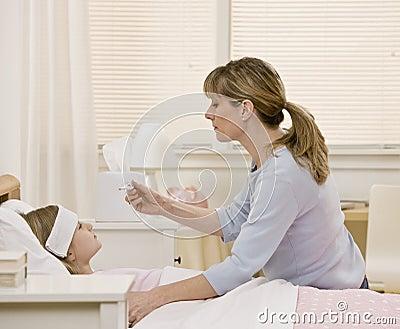 Moeder die de temperatuur van de zieke dochter vergt