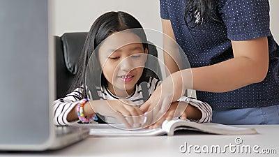 Moeder die dochter leert om met geluk huiswerk te maken voor zelf leren en het concept huisonderwijs selecteert de ondiepe focus stock video