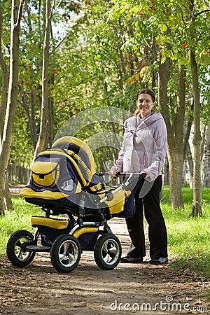 Moeder die met kinderwagen loopt