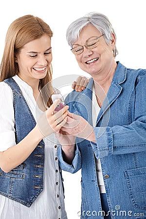 Moeder en dochter die foto s op mobiel bekijken