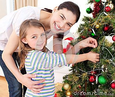 Moeder en haar meisje die een Kerstboom verfraaien