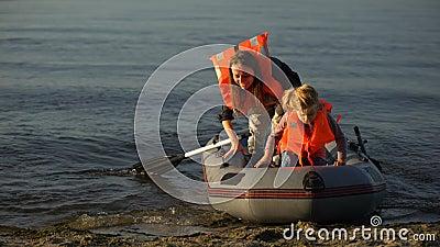 Moeder en kind in levensvesten die van boot naar de wal drijven, vluchtelingen overleefden schipbreuk stock videobeelden