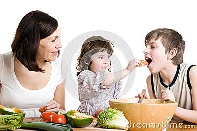 Moeder en kinderen die bij de keuken koken