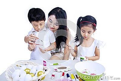Moeder en kinderen die paaseieren schilderen